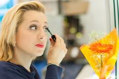 Woman applying mascara. In the mirror Stock Image