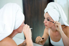 Woman applying mascara in the mirror Royalty Free Stock Photo