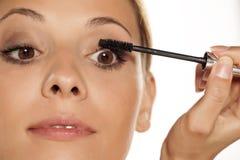 Woman applying mascara. Young beautiful woman applying mascara Stock Photo