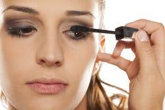 Woman applying mascara. Young beautiful woman applying mascara to her eyelashes Royalty Free Stock Photo