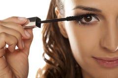 Woman applying mascara. Young beautiful woman applying mascara to her eyelashes Stock Photo