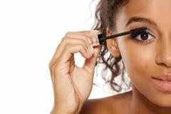 Woman applying mascara. Young dark skinned woman applying mascara to her eyelashes Royalty Free Stock Photo
