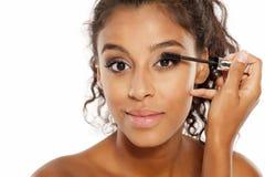 Woman applying mascara. Young dark skinned woman applying mascara to her eyelashes Stock Photography