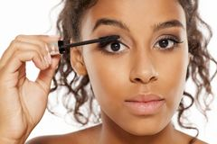 Woman applying mascara. Young dark skinned woman applying mascara to her eyelashes Royalty Free Stock Photography