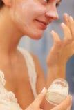 Woman applying mask cream on face in bathroom Stock Photos
