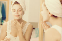 Woman applying mask cream on face in bathroom Royalty Free Stock Photos