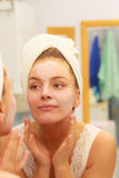 Woman applying mask cream on face in bathroom Stock Photography
