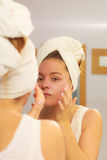Woman applying mask cream on face in bathroom Royalty Free Stock Photography