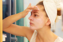 Woman applying mask cream on face in bathroom Stock Images