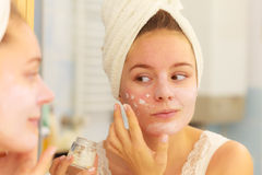 Woman applying mask cream on face in bathroom Royalty Free Stock Images