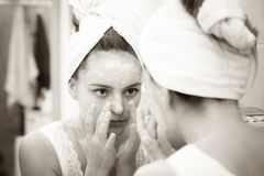Woman applying mask cream on face in bathroom Stock Image
