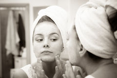 Woman applying mask cream on face in bathroom Stock Photos