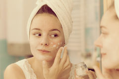Woman applying mask cream on face in bathroom Royalty Free Stock Image