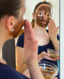 Woman applying mask on her face Stock Images