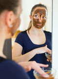 Woman applying mask on her face Royalty Free Stock Photography