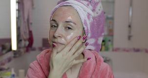 Woman applying mask moisturizing skin cream. Skincare spa. Facial mask. Woman applying mask moisturizing skin cream on face and looking at camera in bathroom stock video