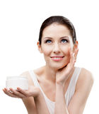Woman applying moisture cream from container on face. Woman putting on moisture cream from container on face, isolated on white. The pursuit of beauty Royalty Free Stock Photos