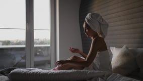 Woman applying moisturiser cream in bedroom.  stock footage