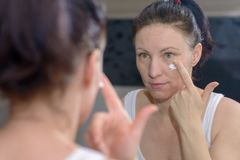 Woman applying a moisturising cream to her cheek. Dabbing it on with her finger while looking at her reflection in a mirror in a skincare and beauty concept Royalty Free Stock Photography