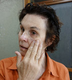 Woman Applying Moisturising Cream To Her Face. A middle-aged woman applies moisturising cream to her cheek Stock Photos