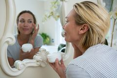 Woman applying moisturizer in bathroom stock images