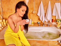 Woman applying moisturizer. At bathroom. Yellow towel Royalty Free Stock Photo