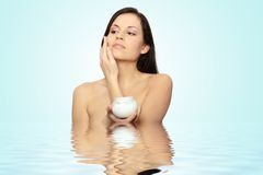 Woman applying moisturizer cream. On face. Close-up fresh woman face Royalty Free Stock Image