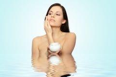 Woman applying moisturizer cream Royalty Free Stock Image