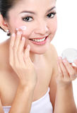 Woman applying moisturizer cream. Beautiful woman applying moisturizer cosmetic cream on face Stock Photography