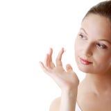 Woman applying moisturizer cream on face Stock Image