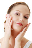 Woman applying moisturizer cream on face. Close-up fresh woman face Royalty Free Stock Image