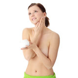 Woman applying moisturizer cream on face Stock Photos