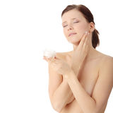 Woman applying moisturizer cream on face Royalty Free Stock Images
