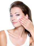 Woman applying moisturizer cream on face Royalty Free Stock Photos