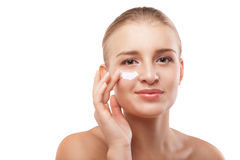 Woman applying moisturizer cream on face isolated. Portrait of young woman applying moisturizer cream on clean fresh face isolated Stock Photos