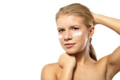 Woman applying moisturizer cream on face isolated Stock Images