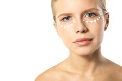 Woman applying moisturizer cream on face isolated. Portrait of young woman applying moisturizer cream on clean fresh face isolated Stock Images