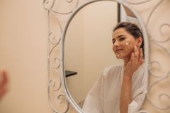 Woman applying moisturizer cream on face. While in the bathroom. Reflection of female looking in to the mirror and putting cosmetic lotion on her face Royalty Free Stock Images