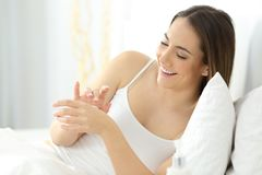 Woman applying moisturizer cream in hands. Happy woman applying moisturizer cream in hands on the bed at home Stock Image