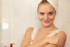 Woman applying moisturizer cream on her body Stock Photos