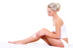 Woman applying moisturizer cream on leg royalty free stock photography