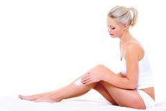Woman applying moisturizer cream on leg. Beautiful pretty woman sitting on bed  applying moisturizer cream on her slim legs Royalty Free Stock Photography