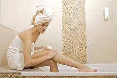 Woman applying moisturizer cream on the legs. Attractive young adult woman applying moisturizer cream on the legs in badroom royalty free stock images