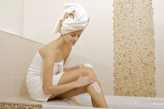 Woman applying moisturizer cream on the legs. Attractive young adult woman applying moisturizer cream on the legs in badroom royalty free stock photo