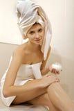 Woman applying moisturizer cream on the legs Stock Images
