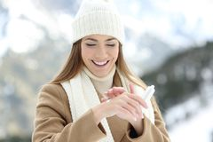 Woman applying moisturizer cream to hydrate hands. Front view portrait of a happy woman applying moisturizer cream to hydrate hands with a snowy mountain in the Royalty Free Stock Images