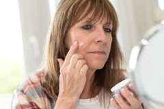 Woman applying moisturizer on her face Royalty Free Stock Image
