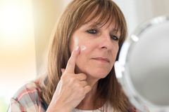 Woman applying moisturizer on her face Stock Photography