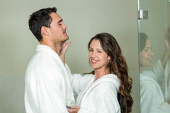 Woman applying moisturizer on man's face Stock Photography
