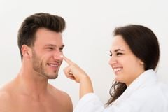 Woman applying moisturizer on man's nose. Happy Young Woman Applying Moisturizer On Man's Nose Over White Background Royalty Free Stock Images